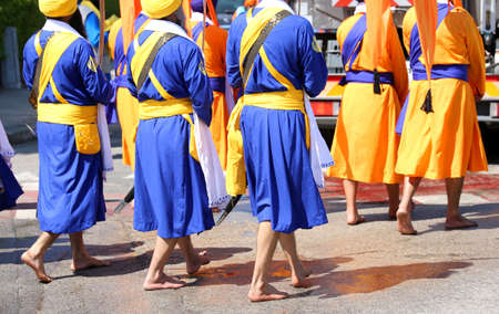 Sikh men dressed in traditional orange and blue dresses participate in a religious rally
