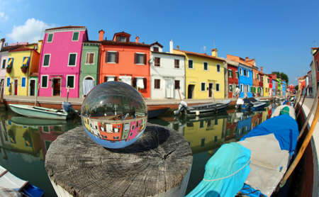 colorful houses on the island of Burano near Venice in Italy and a large glass sphere with the reflection of the village Banco de Imagens