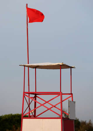 Lifeguard sighting tower in bathhouse with red waving flag means danger
