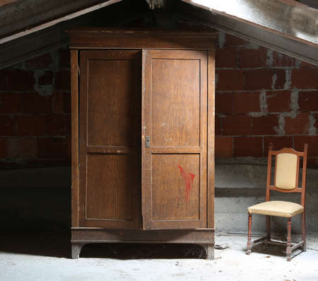 old dusty attic of the house with a wooden wardrobe and an old ramshackle chair