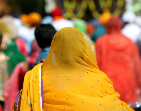 Sikh woman covers her hair with an orange veil during a religious event