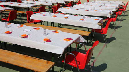 many tables set for a community lunch with many guests Standard-Bild