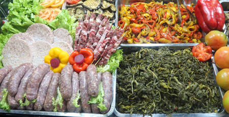 trays full of food at self service restaurant with many sausages spinach peppers skewers and mixed vegetables