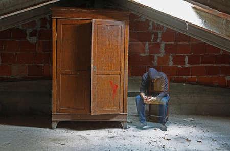 homme fatigué comme une âme assise sur une chaise dans le grenier et une armoire en bois Banque d'images