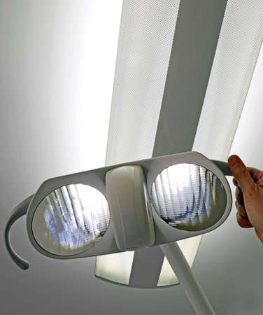 modern lamp of an operating room and the hand of the doctor who adjusts the inclination of the lights