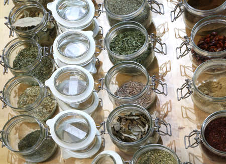 many jars in glass with Spices and herbs for sale on wooden background. Food Archivio Fotografico - 112924547