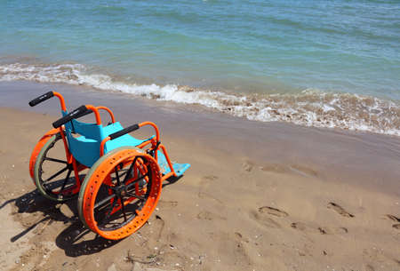 special wheelchair to the beach is placed near the blue sea Stock Photo