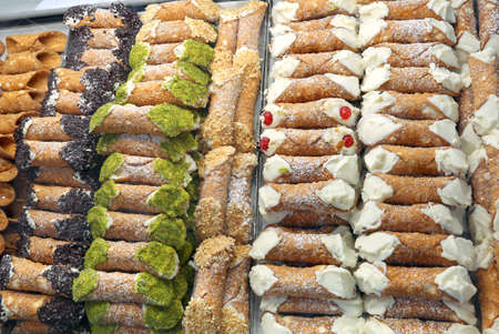 showcase of pastry with many Sicilian cannoli made with ricotta pistachio or chocolate flakes