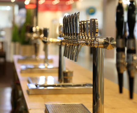 many draft beer taps on the counter of a pub
