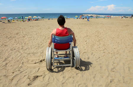 hopeful disabled man in a wheelchair looks at the blue sea