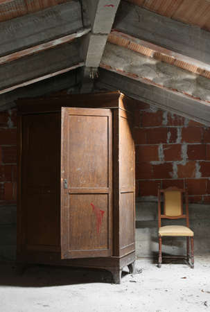 old wooden wardrobe and a chair in the attic of the abandoned house