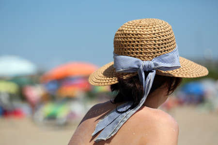 rich woman during tanning with straw hat on the beach of tourist resort village