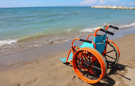 special wheelchair for people with disabilities with large metal wheels to go on the sandy beach or in the sea Stock Photo - 116362050