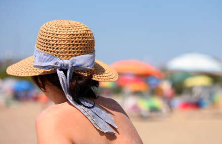 rich woman tans herself in the sun with straw hat on the resort beach