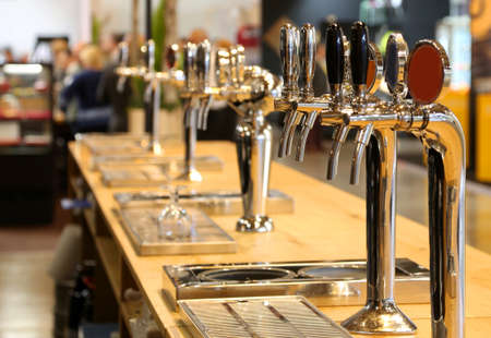 many draft beer taps lined up on the counter of a pub