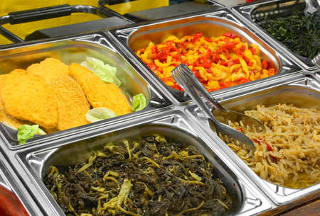 canteen with steel trays containing spinach peppers breaded cutlets