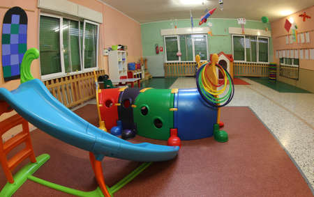 inside a kindergarten with many toys and a plastic slide Stock Photo