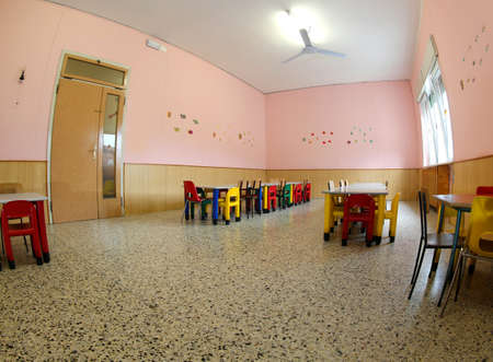 inside the refectory of a school for children with small tables and small chairs suitable for kids