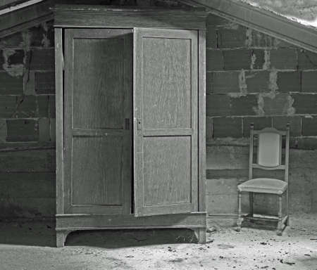 wooden wardrobe and a chair in the uninhabited attic with black and white effect
