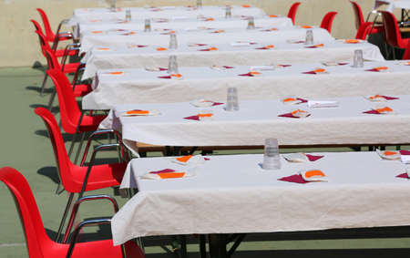 many tables set outdoors with benches for a community lunch