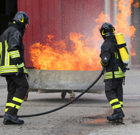 two firefighters with oxygen bottles off the fire during a training exercise Stock Photo