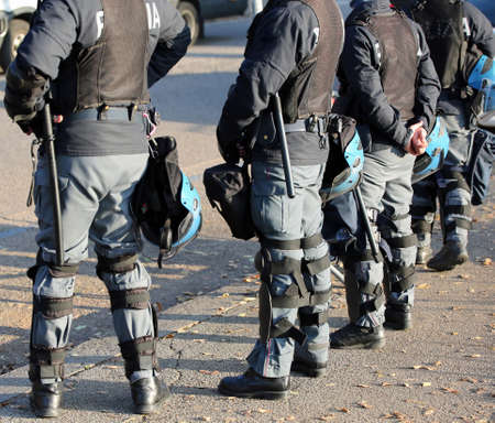 Italian police in riot gear with protective helmets and batons billy
