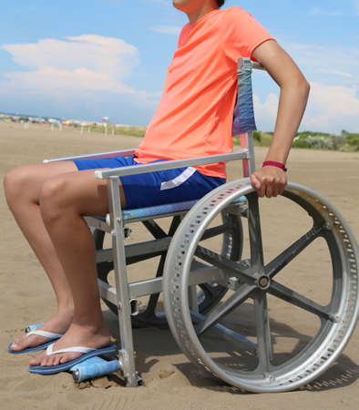 disabled boy on a special wheelchair for the beach Stock Photo