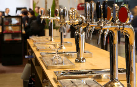 many draught beer taps lined up on the counter of a pub Stok Fotoğraf