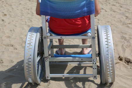 disabled adult man on a special wheelchair for the beach