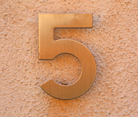golden number 5 on the wall of a house