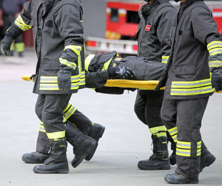 Firefighters carry a wounded man on a stretcher during an exercise
