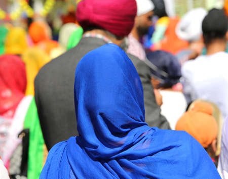 Sikh woman wears a blue veil to cover her hair during a religious celebration