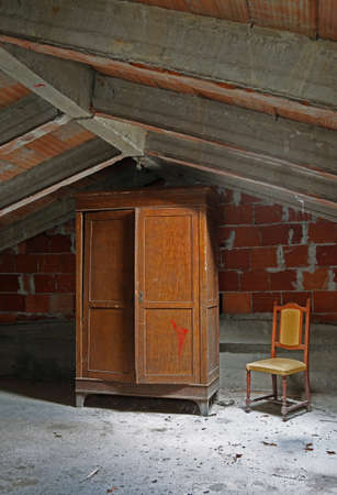 abandoned house with wooden closet and old chair in the attic