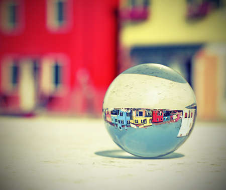 crystal ball with the houses of the island of Burano near Venice and vintage old effect Standard-Bild