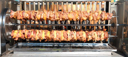 large skewers of chicken and pork meat while cooking very slowly in the big roaster