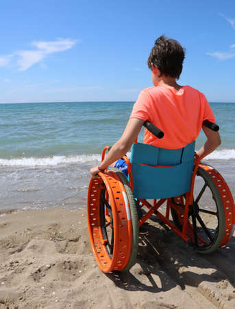 little boy in a wheelchair looks at the sea from the sandy beach in the summer