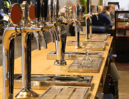 Muchos grifos de cerveza de barril en el mostrador de un pub irlandés Foto de archivo