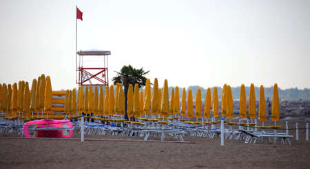 many yellow umbrellas lined up on the beach of a tourist village