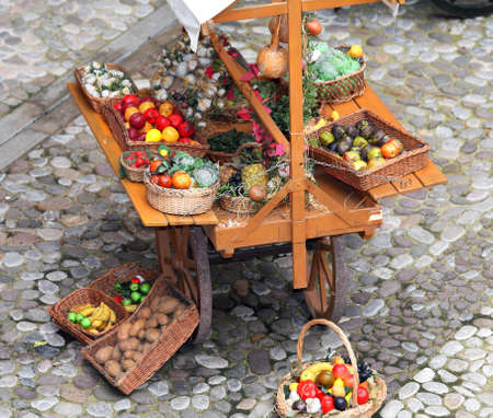 medieval cart of greengrocer with fruit and vegetables for sale on the street Banco de Imagens