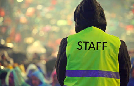 staff guard with the phosphorescent vest at the outdoor concert and during a storm