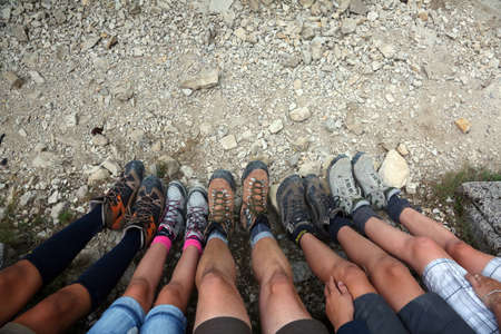 family of five with rock boots in mountain resting after the adventure