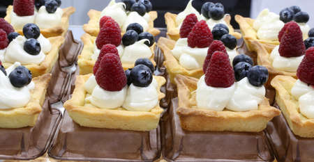 pastries with raspberry and blueberries and custard for sale in the pastry shop