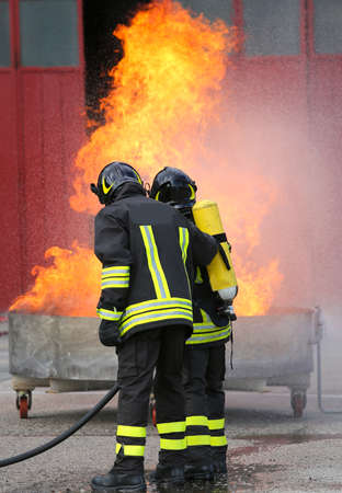 two brave firefighters during the exercise with a tank full of flames and fire and the fireman with oxygen tanks Stock Photo
