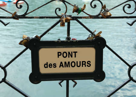 padlocks hanging by the lovers on the bridge with the text PONT de AMOURS which means Bridge of the Lovers in French language Stock Photo