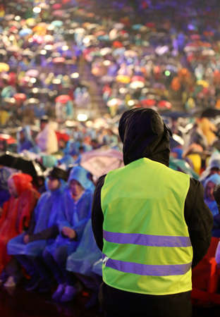 supervisor with high visibility jacket to control the spectators during a live concert Stock Photo