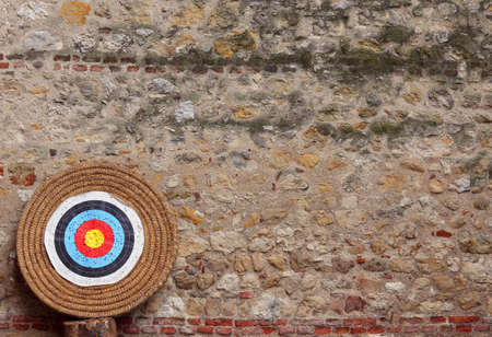 big target with concentric circles to train during the archery competition and ancient wall on background Stock Photo