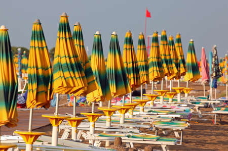 many closed umbrellas on the beach of the sea in late summer without people