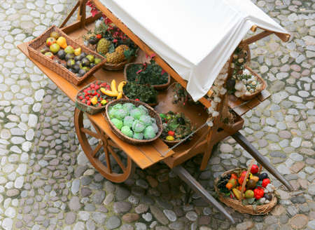 ancient medieval greengrocers cart with fresh fruit and vegetables for sale on the street Stock Photo