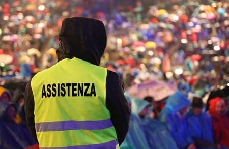 guard with the phosphorescent vest at the concert and during a storm and the text ASSISTENZA that means Assistance in Italian Language
