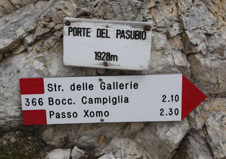 arrow trail marker in mountains with italian text and more place  in Pasubio Mountain  in Italy